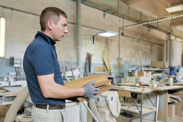 Carpinteiro masculino que fabrica móveis de design de madeira para um pedido particular e individual. fundo de oficina de marcenaria de carpintaria