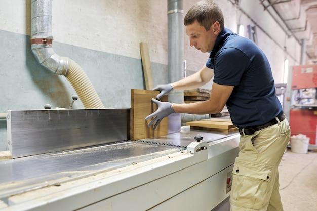 Carpinteiro masculino que faz móveis de madeira para uma ordem particular