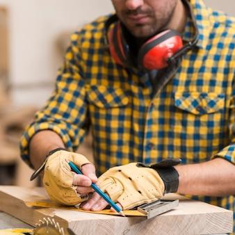 Carpinteiro medindo e traçando linhas com uma régua sobre uma superfície de madeira