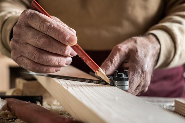 Carpinteiro, medindo uma prancha com um lápis vermelho e uma régua de metal