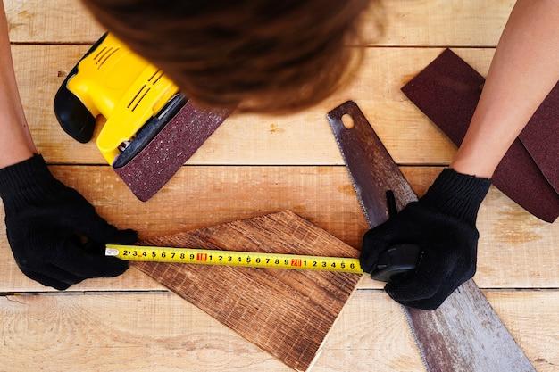 Carpinteiro medindo uma prancha de madeira no local de trabalho com luvas, fazendo produtos artesanais de madeira