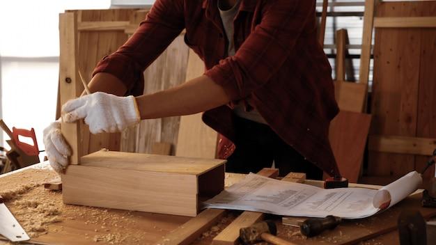Carpinteiro, montagem de pedaços de tábuas no local.
