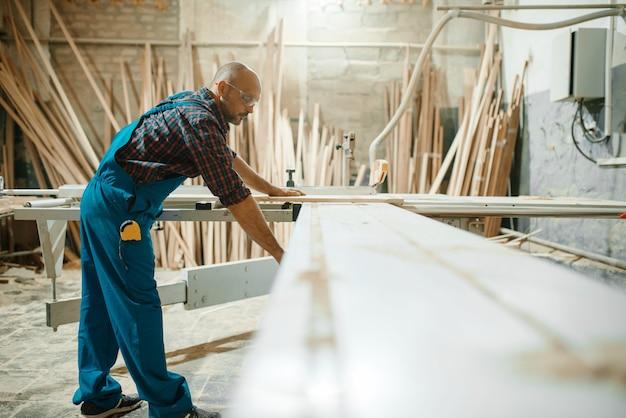 Carpinteiro no pc trabalha com máquina para trabalhar madeira, indústria madeireira, carpintaria moderna.