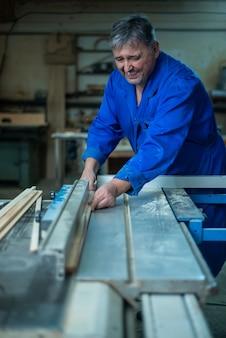 Carpinteiro no trabalho em sua oficina, processamento de madeira em uma máquina para trabalhar madeira