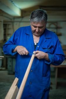 Carpinteiro no trabalho na oficina, um homem faz medições
