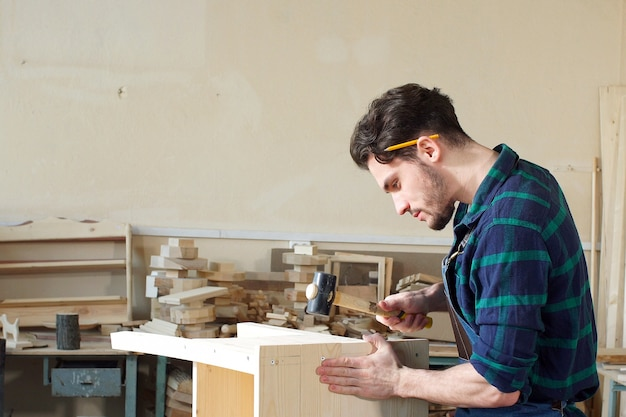 Carpinteiro novo hammering um prego na placa de madeira.
