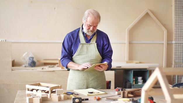 Carpinteiro ou carpinteiro trabalha em uma oficina, fazendo um esboço de uma casa de pássaros, uma casa de pássaros feita de madeira