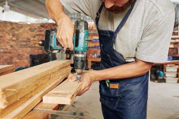 Carpinteiro perfurando prancha de madeira