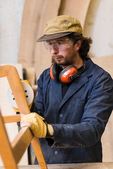 Carpinteiro polimento de móveis de madeira com uma lixadeira de órbita aleatória na oficina