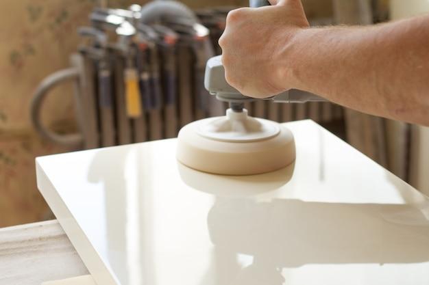 Carpinteiro polimentos da superfície da fachada antes de montar móveis