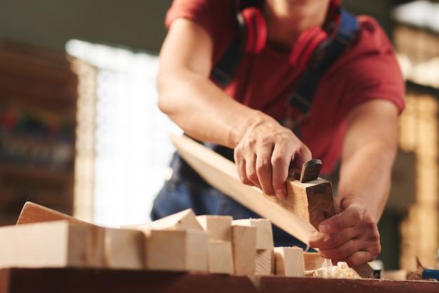 Carpinteiro profissional alisando cuidadosamente a prancha de madeira com a plaina manual