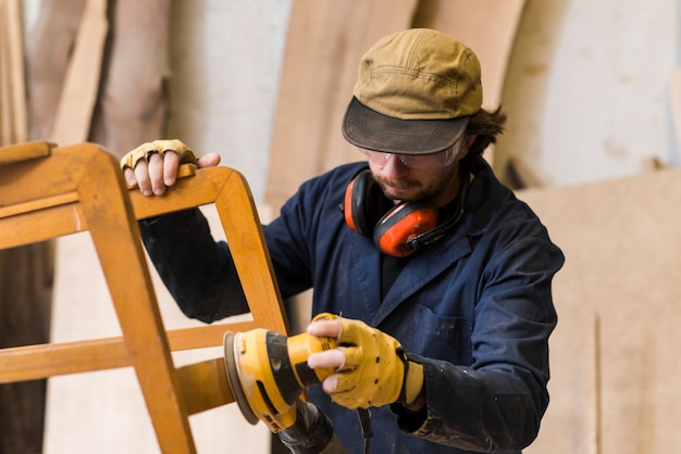 Carpinteiro profissional, polimento de cadeira de madeira com uma lixadeira elétrica