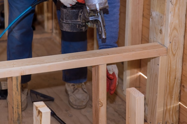 Carpinteiro profissional segurando uma pistola de pregos pneumática nailer de enquadramento na construção da nova casa