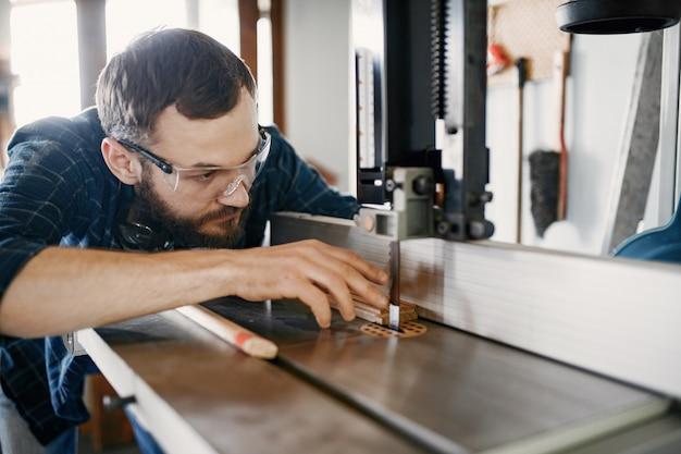 Carpinteiro profissional trabalhando com máquina de serrar