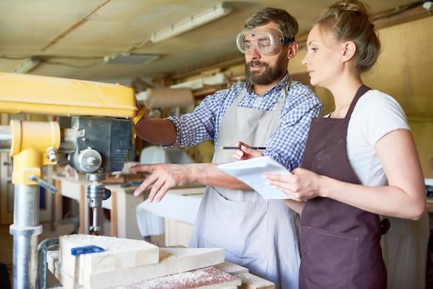 Carpinteiro qualificado que opera a máquina de perfuração