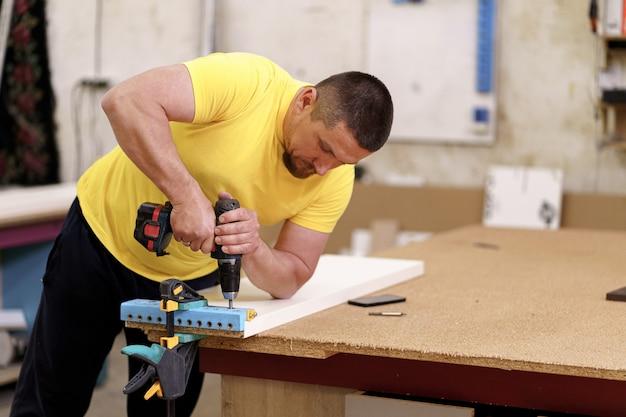 Carpinteiro que trabalha com artesanato em madeira na oficina para produzir móveis de madeira. carpinteiro caucasiano usa ferramentas profissionais para a elaboração. fabricante de diy e conceito de trabalho de carpintaria.