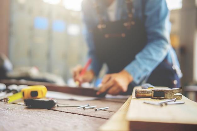 Carpinteiro que trabalha em máquinas do woodworking na loja da carpintaria.