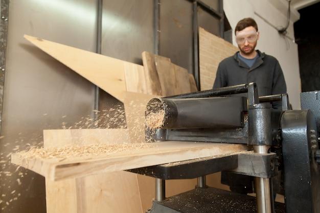 Carpinteiro que trabalha em planadora de energia estacionária com pranchas de madeira