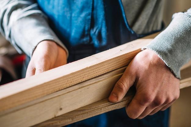 Carpinteiro que transporta madeira