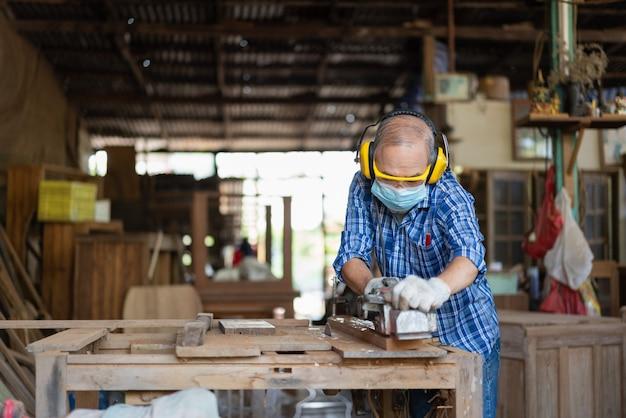 Carpinteiro sênior asiático usa máscara higiênica e protege com plaina elétrica. ajuste a superfície em uma prancha de madeira na oficina de carpintaria