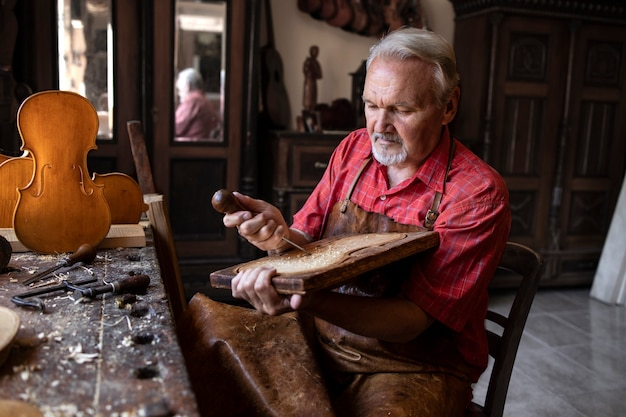 Carpinteiro sênior concentrado, trabalhando pacificamente em sua oficina antiquada em um novo projeto
