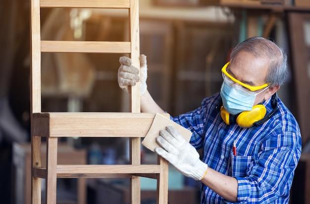 Carpinteiro, sênior, lixa cerca de madeira no local de trabalho usando uma ferramenta de trabalho