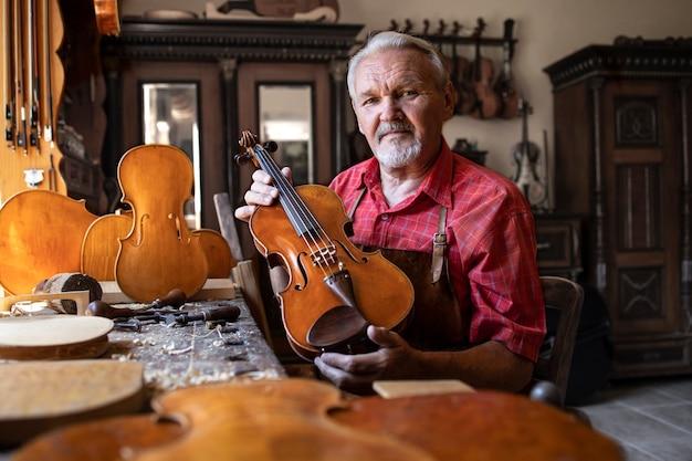 Carpinteiro sênior mostrando o instrumento de violino que ele criou.
