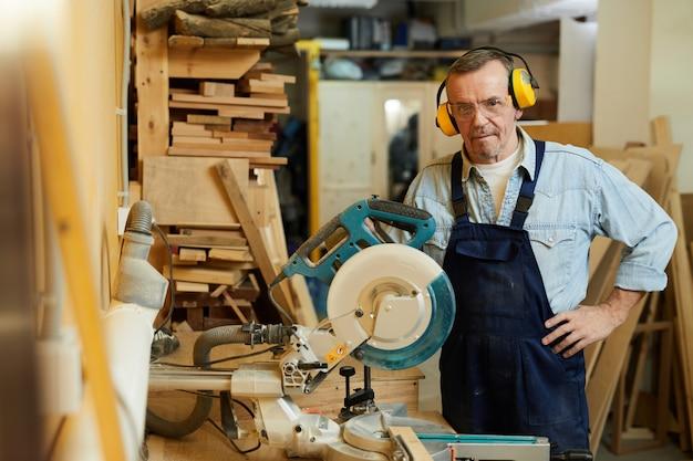 Carpinteiro sênior posando na oficina