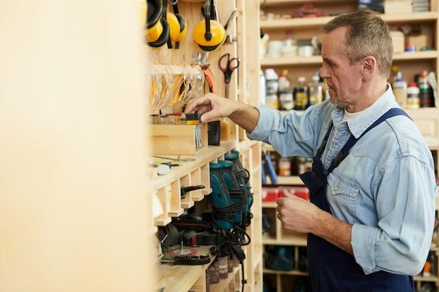 Carpinteiro sênior que escolhe ferramentas