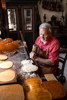 Carpinteiro sênior trabalhador trabalhando em seu projeto criativo na oficina de carpintaria.