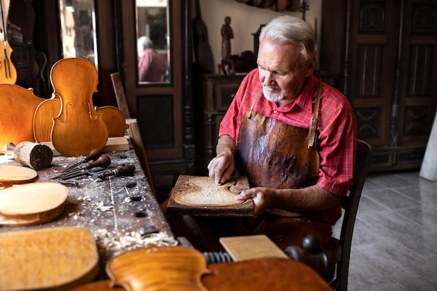 Carpinteiro sênior trabalhando em sua oficina antiquada