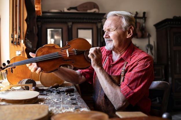Carpinteiro sênior verificando o instrumento de violino que está prestes a consertar