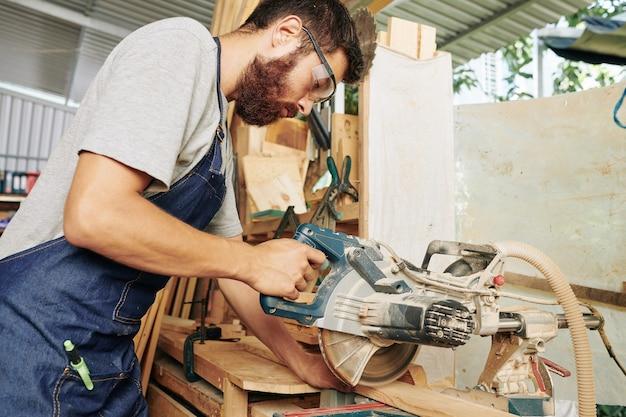 Carpinteiro sério com avental e óculos de proteção cortando madeira com serra circular em sua oficina