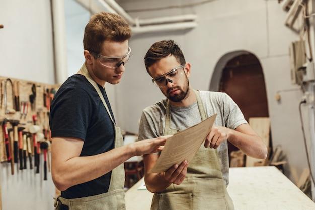 Carpinteiro sério que mostra papéis ao colega