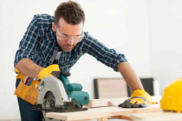 Carpinteiro serrando tábua de madeira