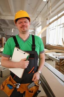 Carpinteiro sorridente segurando a área de transferência