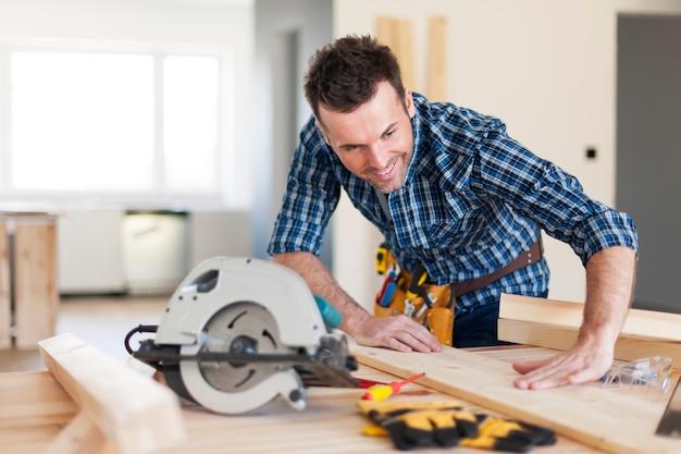 Carpinteiro sorridente verificando o resultado de seu trabalho