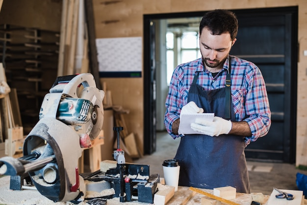 Carpinteiro, tomando um café segurando o caderno na frente da serra circular em sua oficina