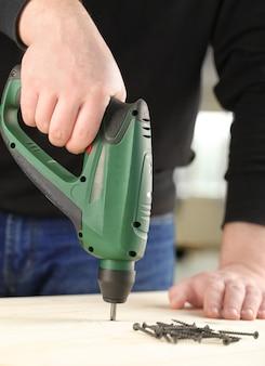 Carpinteiro trabalhando com equipamento elétrico, closeup