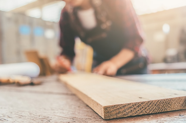 Carpinteiro trabalhando com equipamento na mesa de madeira na loja de carpintaria
