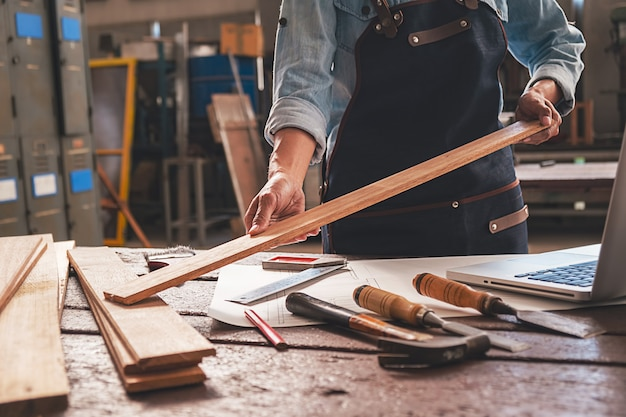 Carpinteiro trabalhando com equipamento na mesa de madeira na loja de carpintaria.