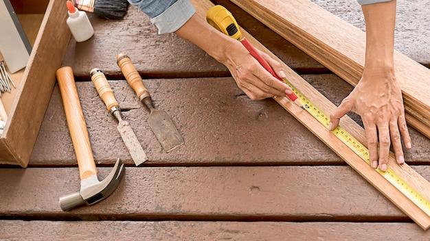 Carpinteiro trabalhando com equipamentos na mesa de madeira na carpintaria.