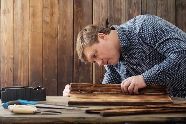 Carpinteiro trabalhando com ferramentas na parede de madeira