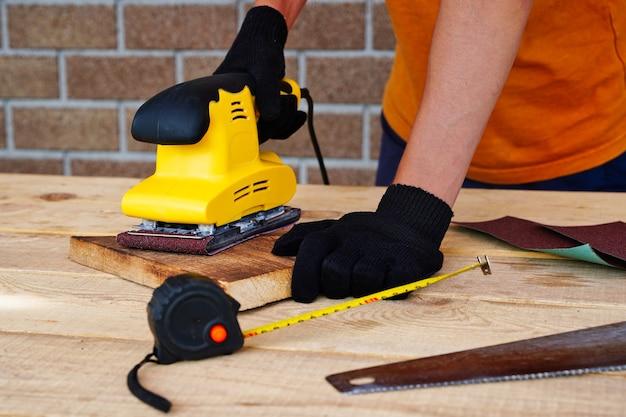 Carpinteiro trabalhando com lixa de madeira e removendo a camada superior com uma lixadeira de polimento de superfície.