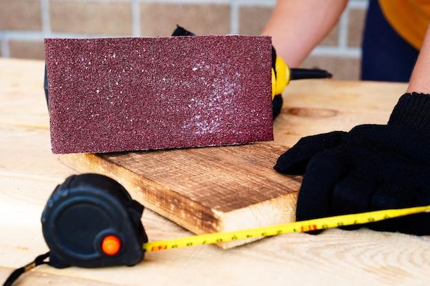 Carpinteiro trabalhando com lixa de madeira e removendo a camada superior com uma lixadeira de polimento de superfície. Foto Premium