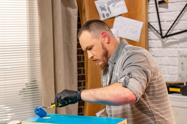 Carpinteiro trabalhando com prancha de madeira e cobre com tinta na oficina