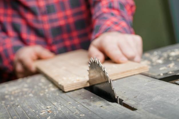 Carpinteiro trabalhando com serra de mesa na oficina. fechar-se.
