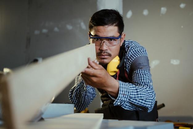 Carpinteiro trabalhando em máquinas para trabalhar madeira em carpintaria, homem fazendo carpintaria em carpintaria.