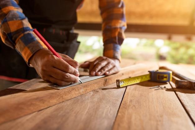 Carpinteiro trabalhando em máquinas para trabalhar madeira em carpintaria. homem trabalha em uma carpintaria usando o primeiro conceito de segurança protetora fones de ouvido.