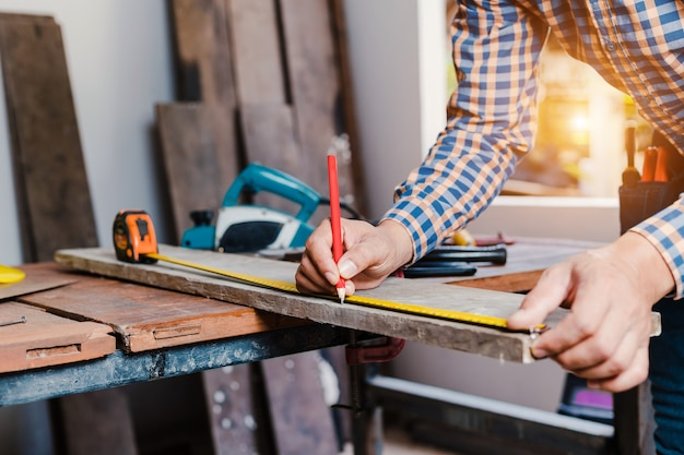 Carpinteiro trabalhando em máquinas para trabalhar madeira na carpintaria.
